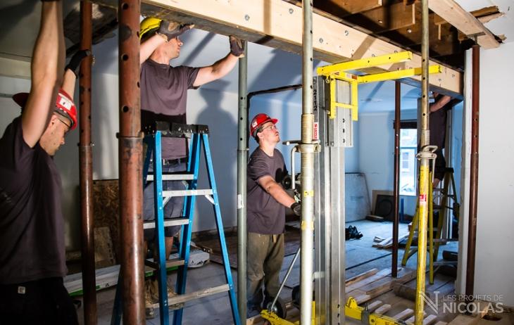 L'équipe de rénovation pose une poutre